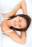 Young smiling woman in bed Stock Photo