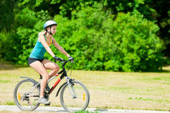 Young smiling woman on bike Royalty Free Stock Photography