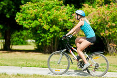 Young smiling woman on bike Royalty Free Stock Photos