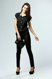 Young smiling woman in black formal clothes standing Royalty Free Stock Image
