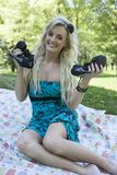 Happy young blonde woman holding black high heel royalty free stock photos