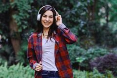 Young smiling woman listening to the music, through headphones on her head. Young smiling woman with bluetooth headphones on her head listening to the music royalty free stock photos