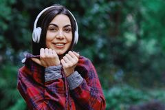 Young smiling woman listening to the music, through headphones on her head. Young smiling woman with bluetooth headphones on her head listening to the music royalty free stock photography