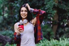 Young smiling woman listening to the music, through headphones on her head. Young smiling woman with bluetooth headphones on her head listening to the music stock photography