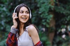 Young smiling woman listening to the music, through headphones on her head. Young smiling woman with bluetooth headphones on her head listening to the music royalty free stock photo