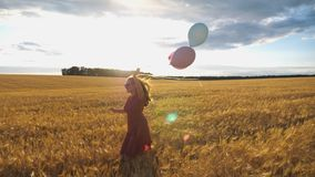 Young smiling woman with brown hair running through golden wheat field with balloons in hand. Beautiful happy girl in. Red dress having fun while jogging among stock video footage
