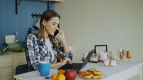 Young smiling woman browsing social media using laptop computer and talking phone during breakfast in the morning stock video footage