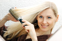 Young smiling woman brushing her long blond hair. Smiling woman brushing her long blond hair Stock Image