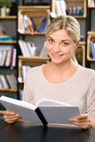 Young smiling woman is busy reading Royalty Free Stock Image