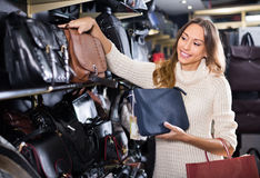 Young smiling woman buying leather purse in shop Royalty Free Stock Photos