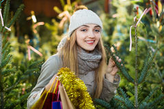 Young smiling woman buying Xmas tree at festive fair Stock Images