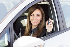 Young smiling woman in car with key in hand. Royalty Free Stock Photography