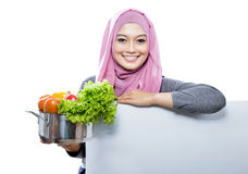 Young smiling woman carrying a pan full of vegetables with hands Royalty Free Stock Photo