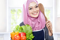 Young smiling woman carrying a pan full of vegetables and wooden Stock Photo