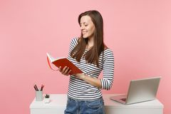 Young smiling woman in casual clothes holding notebook work standing near white desk with contemporary pc laptop stock photo
