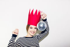 Young smiling woman celebrating party, wearing stripped dress and red paper crown, happy dynamic carnival disco ball Royalty Free Stock Images