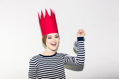 Young smiling woman celebrating party, wearing stripped dress and red paper crown, happy dynamic carnival disco ball. Young smiling woman on white background Royalty Free Stock Photo