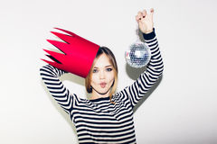Young smiling woman celebrating party, wearing stripped dress and red paper crown, happy dynamic carnival disco ball. Young smiling woman on white background Stock Photos