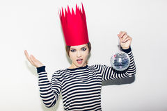 Young smiling woman celebrating party, wearing stripped dress and red paper crown, happy dynamic carnival disco ball. Young smiling woman on white background Royalty Free Stock Photos