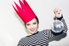 Young smiling woman celebrating party, wearing stripped dress and red paper crown, happy dynamic carnival disco ball Royalty Free Stock Photo