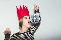 Young smiling woman celebrating party, wearing stripped dress and red paper crown, happy dynamic carnival disco ball. Young smiling woman on white background Stock Image