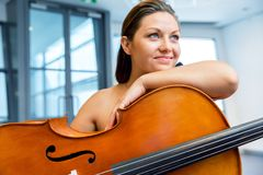 Woman with a cello. Young smiling woman with a cello royalty free stock image
