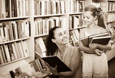 Young smiling woman with child  in bookstore Royalty Free Stock Image
