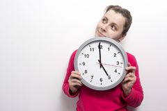 Young smiling woman with classic clock look at side. Time woman concept. Brunette girl holds watch clock against white wall. Young smiling woman with classic Royalty Free Stock Images