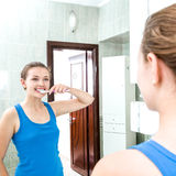 Young smiling woman cleaning teeth Royalty Free Stock Image