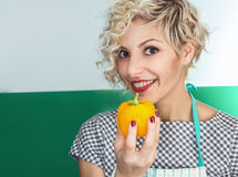 Young smiling woman cook holding pepper Stock Images