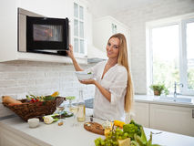 Young smiling woman cooking at the kitchen Stock Photography