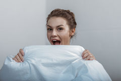 Young smiling woman covering face with bedcover in bed Stock Images