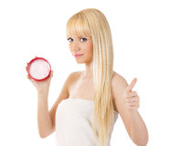 Young smiling woman with cream giving thumbs up Royalty Free Stock Photos