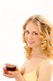 young smiling woman with cup of tea in sunlight Royalty Free Stock Image