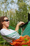 Young smiling woman in dark sunglasses lies in hammock outdoors. And works on notebook stock image