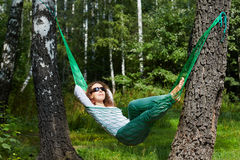 Young smiling woman in dark sunglasses lies in hammock. Turning his face to the sun and putting her hands behind her head stock photography