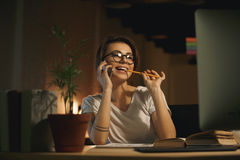 Young smiling woman designer talking by mobile phone Royalty Free Stock Image