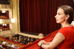Young smiling woman in dress sitting in theatre. Young smiling woman in red dress sitting on balcony in the theatre Royalty Free Stock Photography