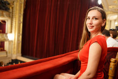 Young smiling woman in dress sitting in theatre. Young smiling woman in red dress sitting on balcony in the theatre Stock Image