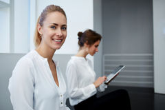Young smiling woman dressed in formal wear posing while her partner sitting near and working on digital tablet, Stock Image