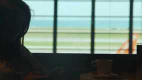Young smiling woman drinking coffee in airport cafe, typing message on cellphone. Stock footage stock video