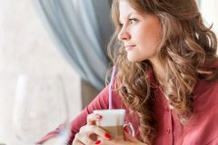 Young smiling woman is drinking coffee in a cafe Royalty Free Stock Photo