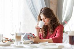 Young smiling woman is drinking coffee in a cafe Stock Image
