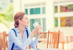 Young smiling woman drinking coffee outside corporate office Stock Image