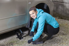 Young smiling  woman driver changes car tyres Stock Photos