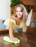 Young smiling woman dusting table Stock Photography