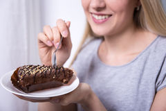 Young smiling woman eating chocolate cake at home Royalty Free Stock Images