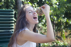 Young smiling woman eating grapes in vineyard. Stock Photos