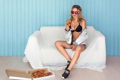 Young smiling woman eating a piece of pizza drinking juice sitting on sofa wearing sunglasses Royalty Free Stock Photos