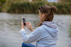 Young smiling woman with a phone listens to music Stock Photos